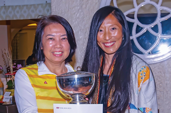 Vera Yuen (left), spouse of Cathay Pacific Catering Services staff, receives the Rose Bowl trophy from Mrs. Healy.