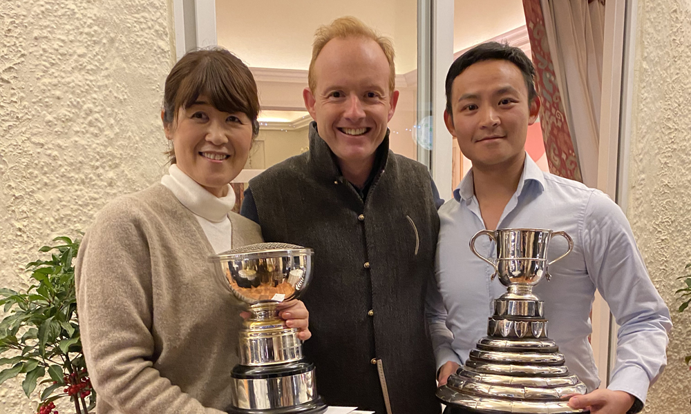 The winner of the Rose Bowl, Yumiko Noguchi, and the winner of the Scott Cup, Matthew Young, receive the trophies from Merlin Swire.